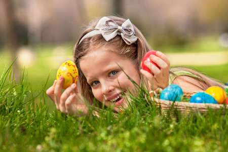 Foto per Happy child lying on green grass. and find easter egg outdoor. - Immagine Royalty Free