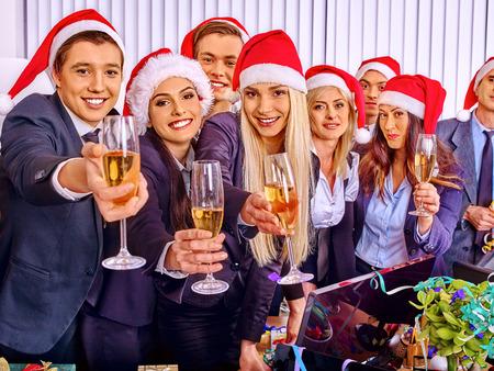 Foto de Happy business group people in santa hat at Xmas corporate party. - Imagen libre de derechos