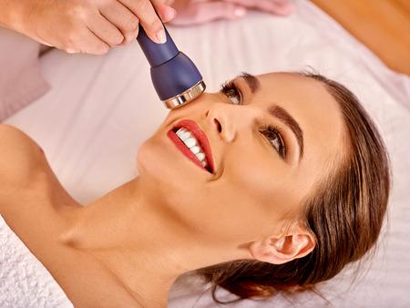 Photo pour Young woman receiving electric facial massage at beauty  electroporation equipment. - image libre de droit
