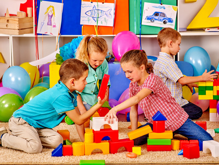 Group children build blocks on floor in kindergarten .