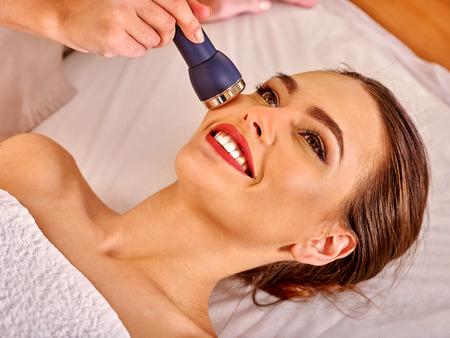 Photo pour Portrait of young smiling woman receiving electric ultrusound facial massage at beauty salon. - image libre de droit