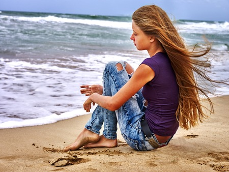 Photo for Summer girl sea.  Young girl sitting and dreams on coast near ocean with waves. - Royalty Free Image