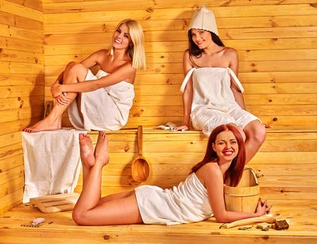 Happy group of girlfriends luxuriate in sauna.