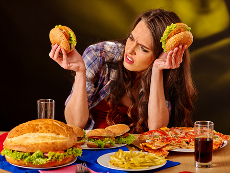 Unhappy girl eat cheap fastfood big hamburger and pizza .