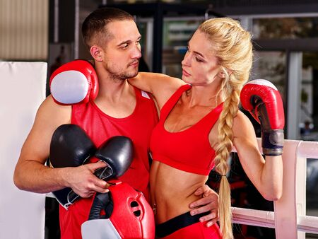 Female boxer in red with your male coach after workout in gym