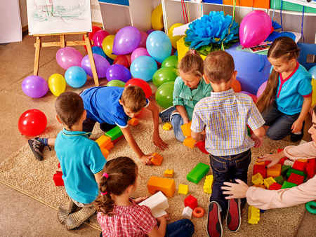 Group children game blocks on floor in kindergarten . Balloons on floor Top view.