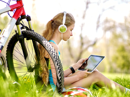 Bikes cycling girl. Girl rides bicycle. Girl wearing headset in cycling watch in pc tablet near bicycle. Cycling is good for health. Cyclist looking pc tablet.