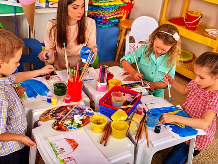 Photo pour Children painting on paper at table in primary school. Teacher woman learn children paint. - image libre de droit