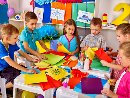 Foto de Group kids are making something out of colored paper in primary school. - Imagen libre de derechos