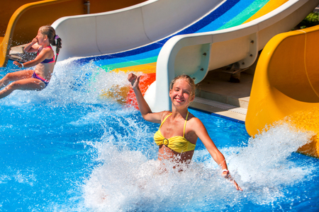 Photo for Two children on water slide at aquapark and thumb up. Summer holiday. There are two water slides in aqua park. Outdoor. Water children holiday. - Royalty Free Image
