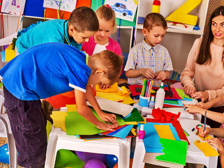 Photo pour Children cutting paper in class. Kids development and social lerning children in school. Childrens project in kindergarten. Low tables for work and creativity. Group girl , boy with teacher together. - image libre de droit