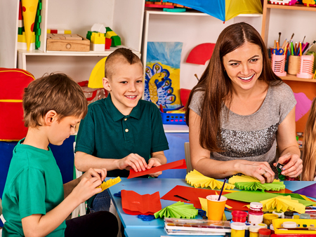 Preschool scissors in kids hands cutting paper with teacher in class room. Development and social lerning happy children in school. Childrens project in kindergarten. Small group girls together.