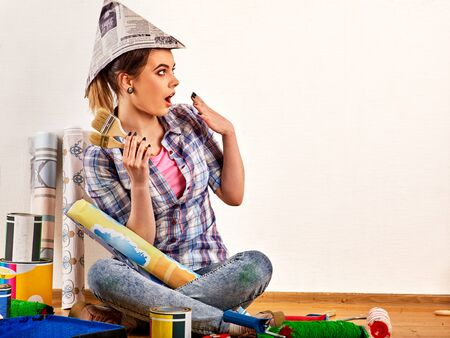 Repair home woman holding paint brush for wallpaper. Female in newspaper cap renovation apartment. Paint bank and roll paper background . Student earns extra money at construction site.