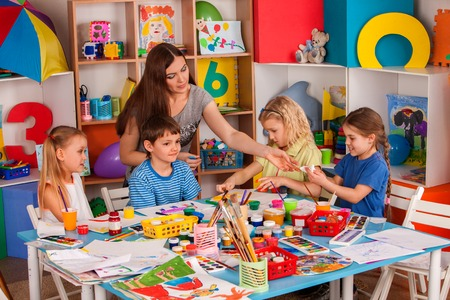 Foto de Kids playroom organization of children painting and drawing in kids club. Craft lesson in primary school. Teaching children to do common project. - Imagen libre de derechos