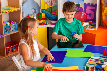 Photo for School children with scissors in kids hands cutting paper with teacher in class room. Childrens project in kindergarten. Large group girls and boys together. Origami exhibition. - Royalty Free Image
