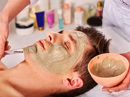 Photo pour Mud facial mask of man in spa salon. Cleansing massage with clay full face. Lying man on therapy room for skin detox. Beautician with bowl therapeutic procedure. Anti-aging cosmetic mask. - image libre de droit