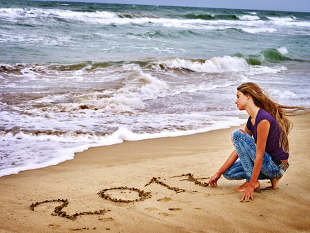Photo for Summer girl sea.  Girl is writting in sand  2017 near ocean with waves. Sea concept. - Royalty Free Image