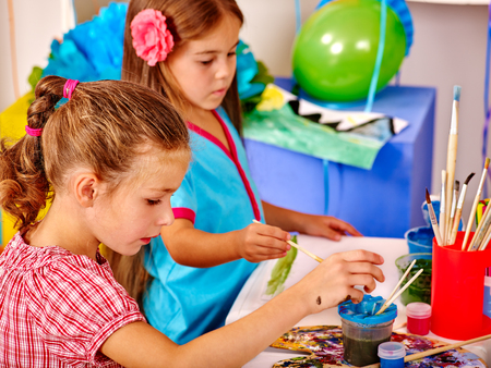 Photo pour Girls keep brush painting on table in kindergarten . Painting learning. - image libre de droit
