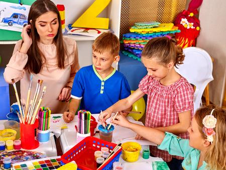 Foto de Kids with teacher woman painting on paper at table  in  kindergarten school. Painting school. - Imagen libre de derechos