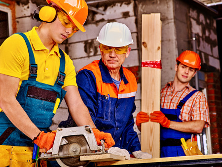 Photo pour Happy group people  of three people builder with circular saw. - image libre de droit