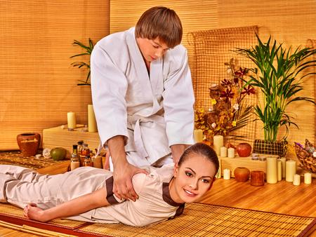 Photo pour Man in white uniform making bamboo massage of beautiful woman. - image libre de droit