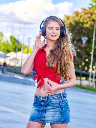 Foto de Girl in headphones and denim listens to music with closed eyes and sidewalk walking in city alone. - Imagen libre de derechos