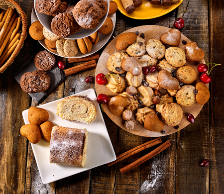 Oatmeal cookies and sand chocolate cake with cherry berry and crispy wafer rolls with cream on cutting board on wooden table in rustic style. Easily digestible and quickly digestible substances.