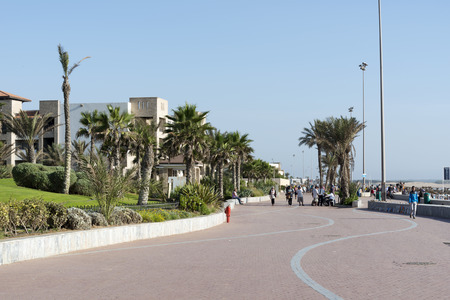 Promenade along the beach with the walking vacationing people in Agadir, Marocco