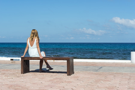 Woman sitting on the bench main promenade looking at the ocean on the Isla Mujeres in Mexico