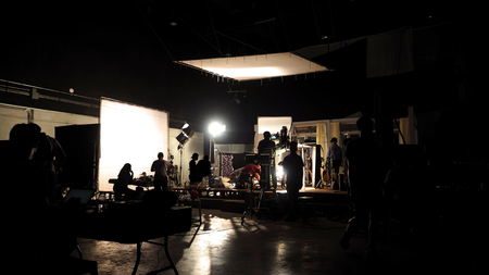 Photo pour Behind the scenes of video shooting production crew team silhouette and camera equipment in studio.  - image libre de droit
