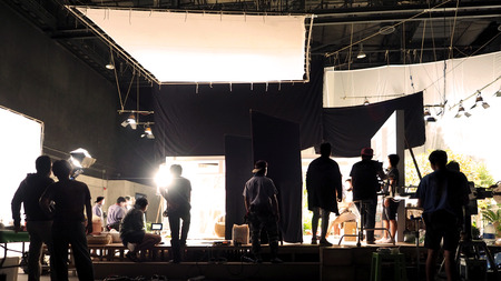 Photo pour Silhouette of people working in big production studio for shooting or recording movie video by digital camera and lighting set. - image libre de droit