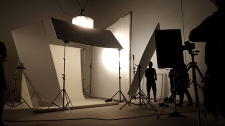 Photo pour Silhoutte images of video production and lighting set for filming which movie crew team working and silhouette shadow of camera and professional equipment in big studio for commercial advertising. - image libre de droit