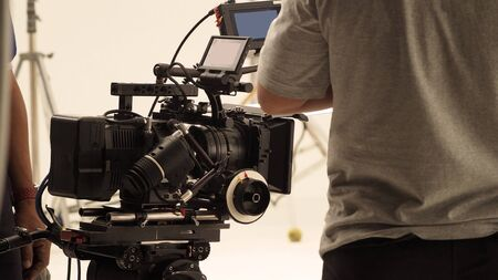Photo pour Behind the shooting production crew team and hd video camera and equipment in studio which includes big tripod, soft box light, monitors, lens for making online web film or movie or live broadcasting  - image libre de droit