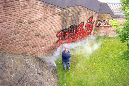 GERMANY, FRANKFURT AM MAIN - May 07.2014 : Worker of municipal service of city cleans a wall from graffiti