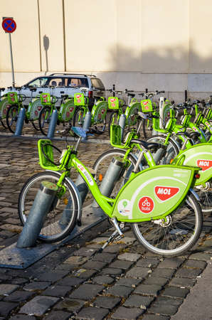 Budapest, Hungary - Nov 6, 2019: Public green bikes for rental in the center of the Hungarian capital. Bike-sharing. Eco-friendly means of transport. Ecological measures in the cities. Vertical photo.