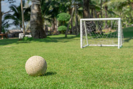 Photo for Soccer ball in grass field in front of the goal post. Football ball on green grass of playground. - Royalty Free Image