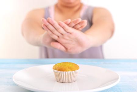 Foto de fat woman rejecting cupcake or unhealthy food. Health care concept. - Imagen libre de derechos