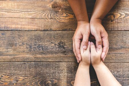 Photo for Top view of couple holding hands at a wooden table. - Royalty Free Image