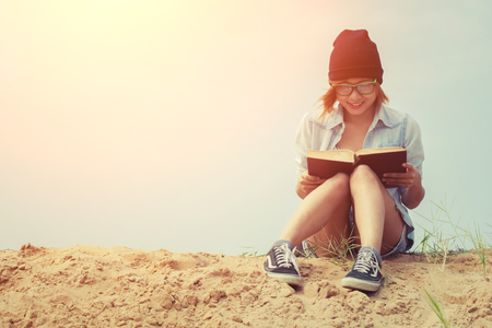 Photo pour Young girl reading book and sitting on the beach with sunrise - image libre de droit