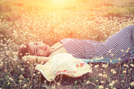 Photo pour Young sexy woman lying in grass nearing her hat and smiley to camera - image libre de droit