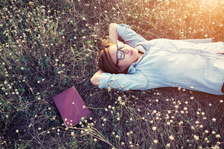 Beautiful young hipster laying down on the meadows field smiley
