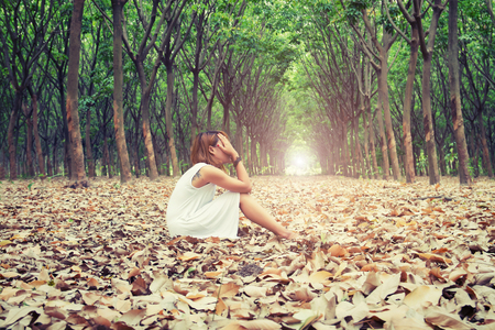Photo pour Sad woman hands off her face so sadly sitting on dry leaf in the forest - image libre de droit