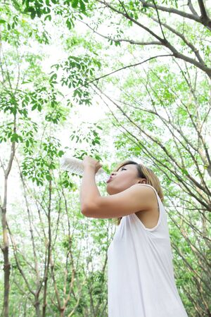 Portrait of young beautiful  woman wearing white dress drinking water in the green forest