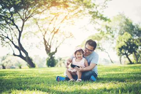 Photo pour Father and daughter smiling using smartphone in the park - image libre de droit