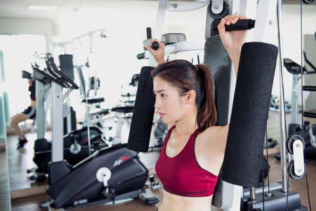 Young fitness woman executed exercise with exercise-machine in gym.