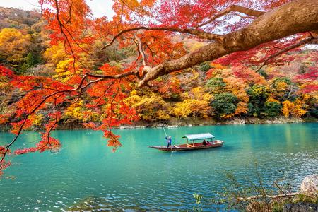 Photo for Boatman punting the boat at river. Arashiyama in autumn season along the river in Kyoto, Japan. - Royalty Free Image