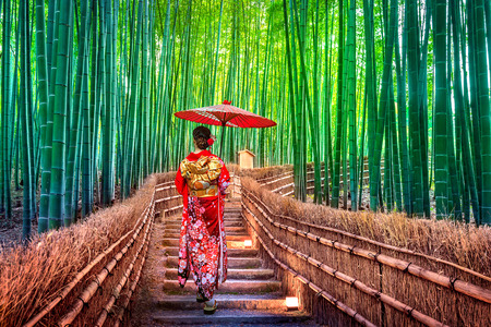 Foto de Bamboo Forest. Asian woman wearing japanese traditional kimono at Bamboo Forest in Kyoto, Japan. - Imagen libre de derechos