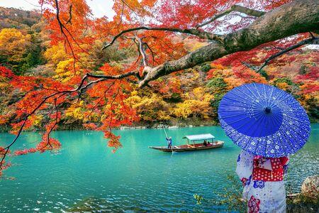 Photo pour Asian woman wearing japanese traditional kimono at Arashiyama in autumn season along the river in Kyoto, Japan. - image libre de droit