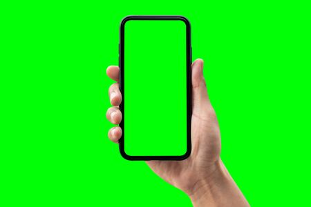 Photo pour Hand holding smartphone isolated on green background. - image libre de droit