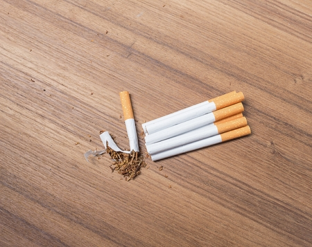 stop smoking Tobacco ,tear cigarette detrimental on wood background , and space for add text above ,select focus front